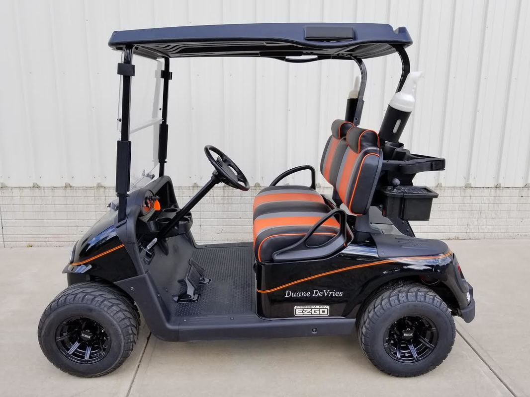 2012 E-Z-GO RXV Electric 48-V, New Trojan Batteries, Black, Custom Orange & Black Seats, Black Top, Head & Tail Lights, Dual USB, Orange Pinstripe, Custom Decals, Clear Windshield, Carbon Fiber Ball Washer, Sandbottles, 10'' Eight Spoke Gloss Black Wheels, Refurbished